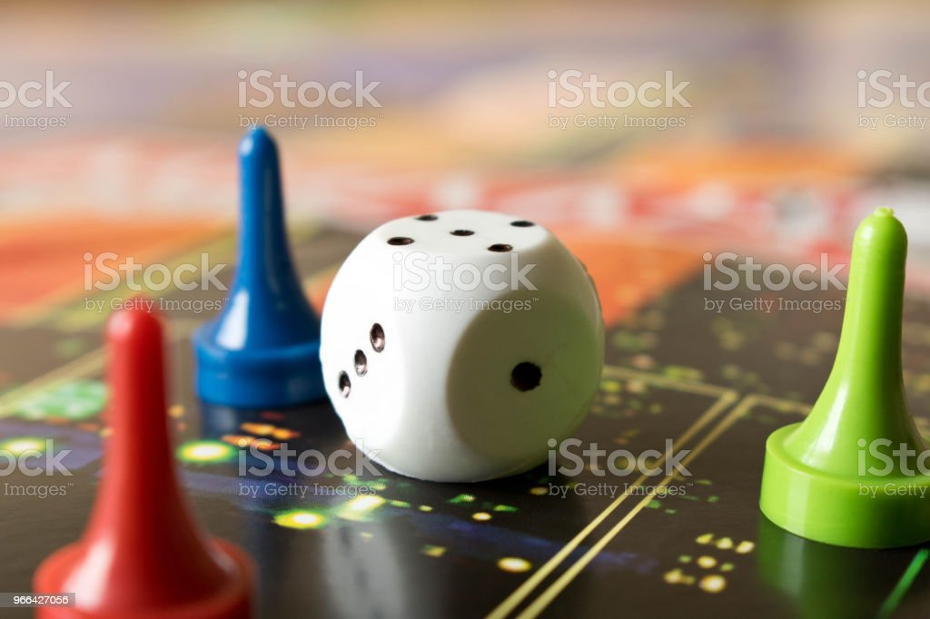 Multi-colored game chips with dice on the playing board. Board game.