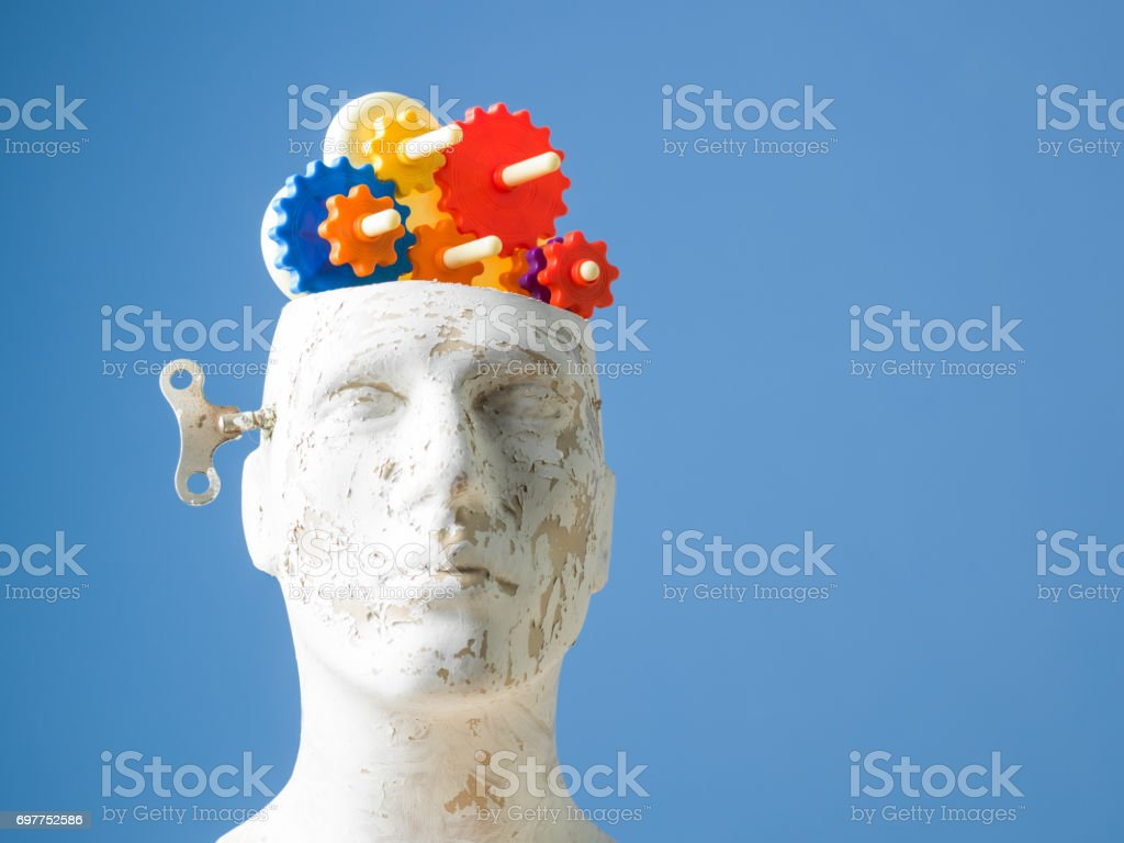 Multicolored Gears In Mannequin Head On Blue Bakcground stock photo