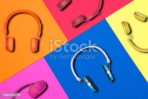 Multicolored headphones on colorful paper background. Colorful headphones music accessory studio design.