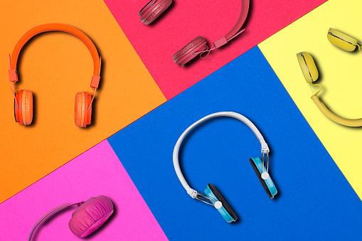 Multicolored headphones on colorful paper background. Colorful headphones music accessory studio design.