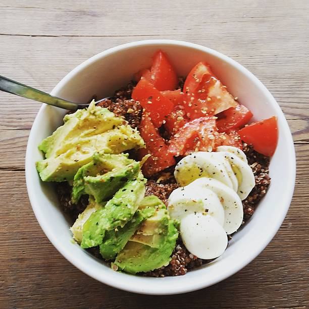 Multicolored Healthy Organic Local Fresh Quinoa Bowl Lunch Williamsburg Brooklyn This is a square, color, royalty free stock photograph overhead shot of a healthy prepared lunch with organic produce and fruits. The quinoa filled bowl is topped with avocado, tomato and hard boiled eggs. Photographed with a Samsung Galaxy S5 mobile phone. taken on mobile device stock pictures, royalty-free photos & images
