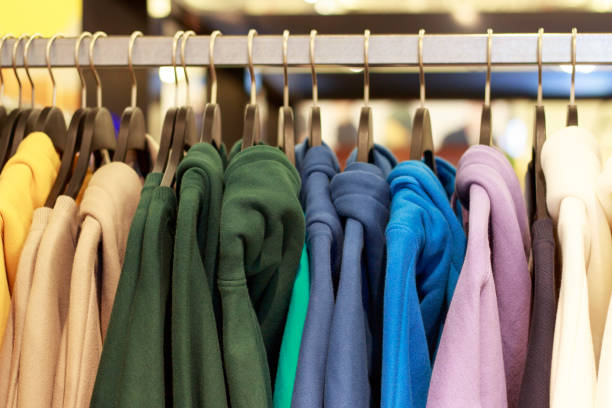 Multicolored hoodies on hangers in a sports store close-up, clothing concept stock photo