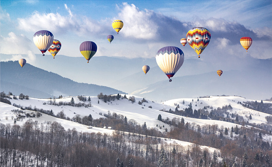Multicolored hot air balloons on a mountain ridge covered snow
