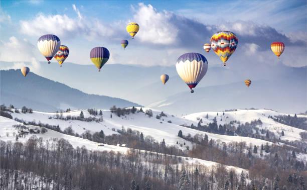 bunte heißluftballons auf einem bergrücken bedeckt schnee - eis ballons stock-fotos und bilder