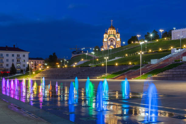 Cтоковое фото Multi-colored jets of the fountain and St. George Church in Samara