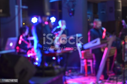 Multicolored light blurred background  of  music band singing  on a stage at a concert