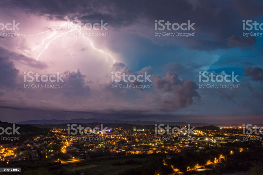 Multi-colored lightning storm over bright city at night stock photo