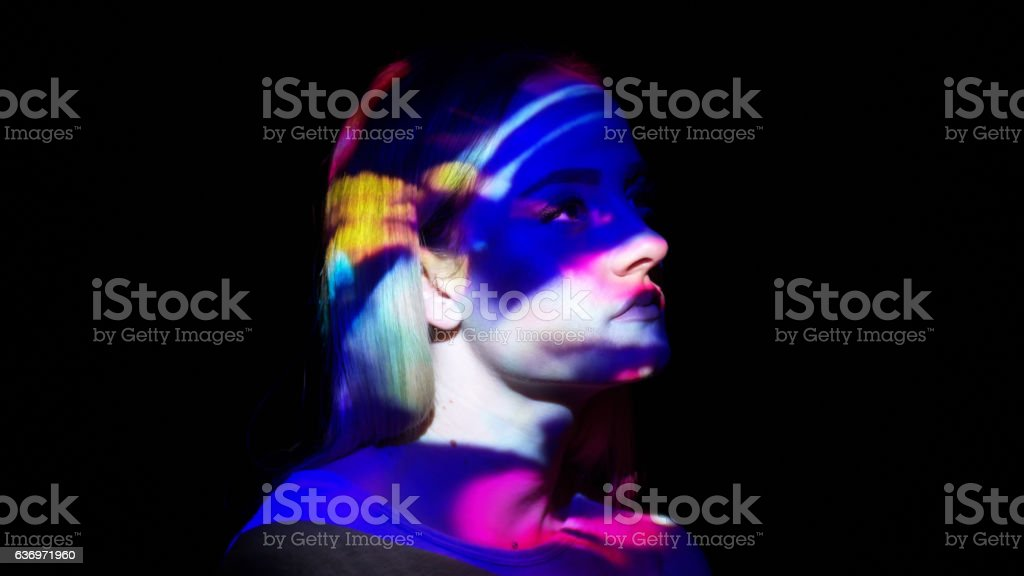 Multicolored lights on a woman's face stock photo