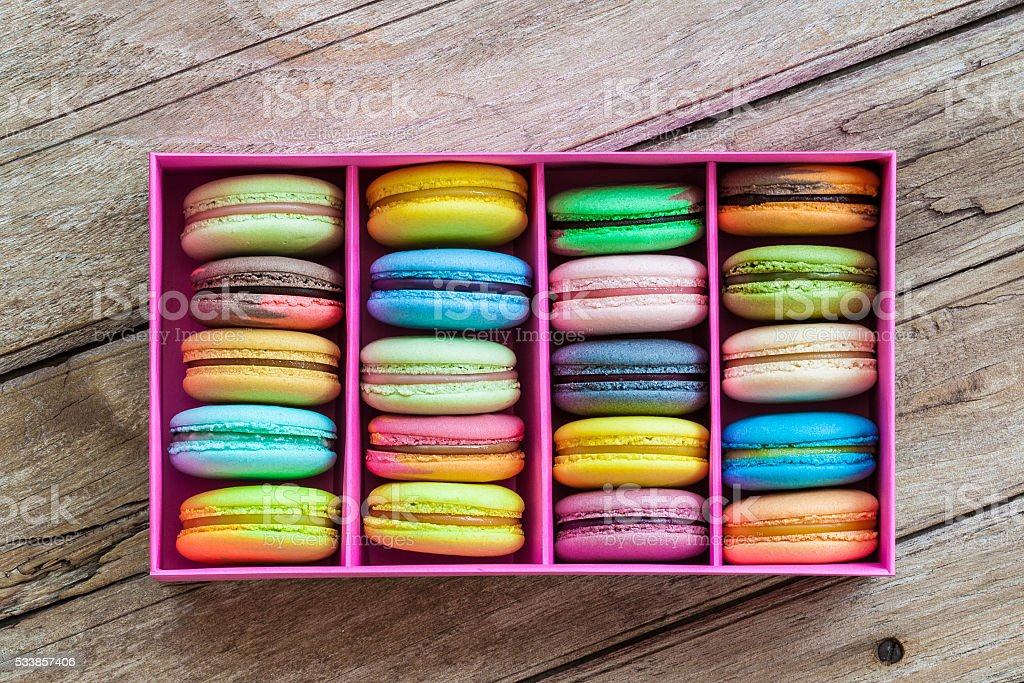 Multicolored macaroon different lie in the pink cardboard box stock photo