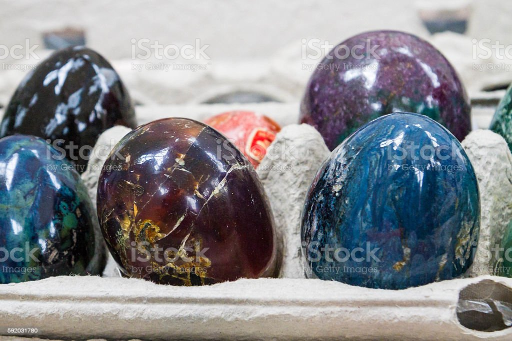 Multicolored marble eggs of stone in cells stock photo