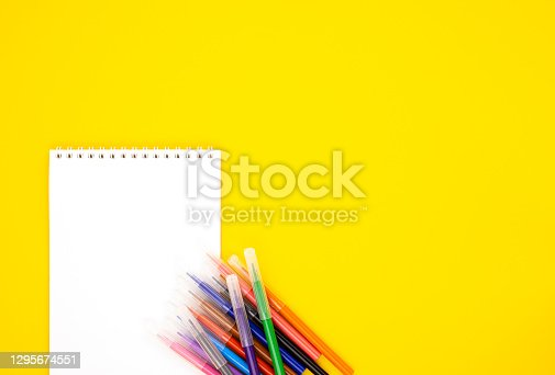 istock multi-colored markers with a white blank Notepad on a yellow background, space for text 1295674551