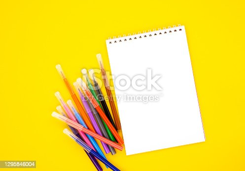 istock multi-colored markers with a white blank Notepad on a yellow background, space for text 1295846004