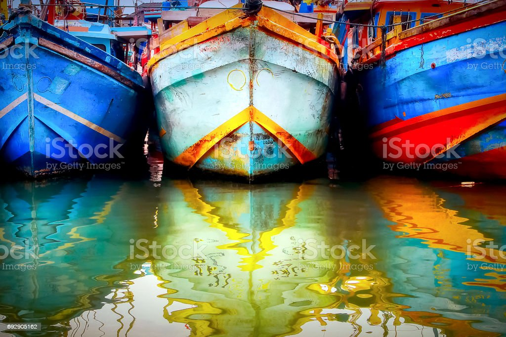 Multicolored old boat in the fishing port. Colored reflections in the water. Sri Lanka. Tangalle. stock photo