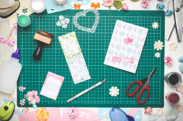 Multi-colored paper, homemade postcard and scrapbooking tools on green cutting mat