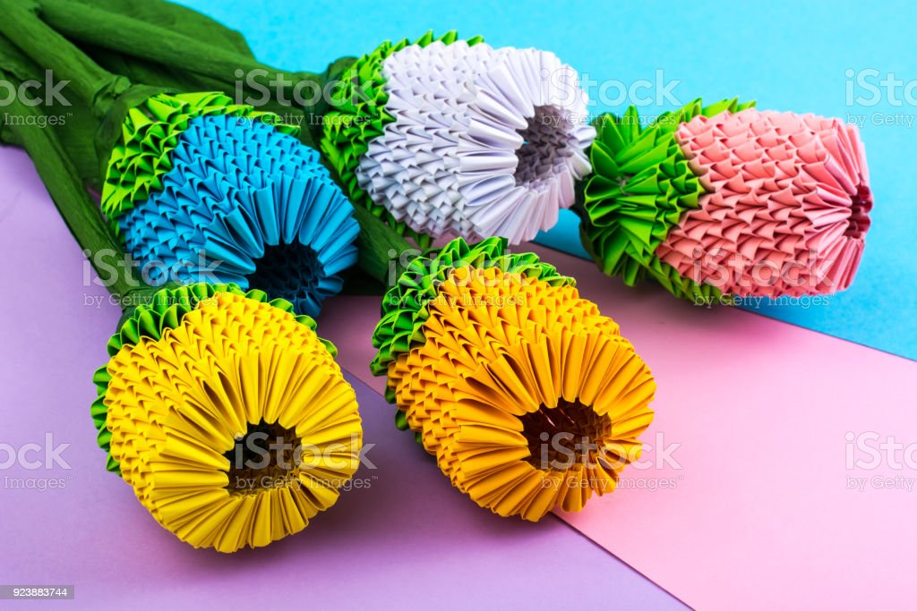 Multicolored Paper Origami Flowers On Pastel Background Stock Photo