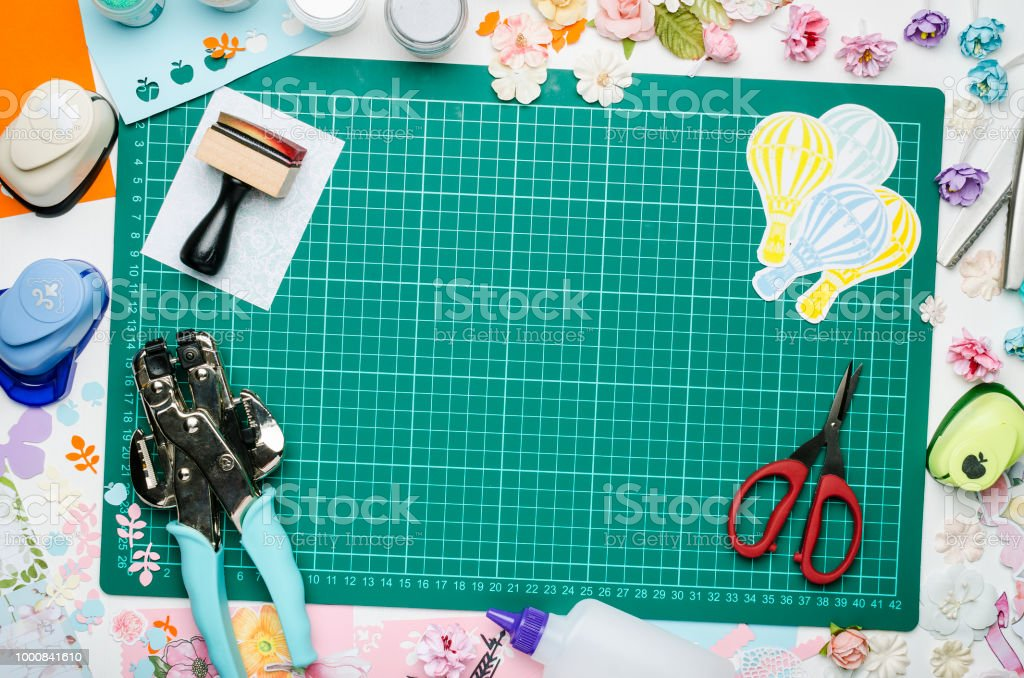 Multicolored Paper Scrapbooking Tools And Materials On Green Mat For