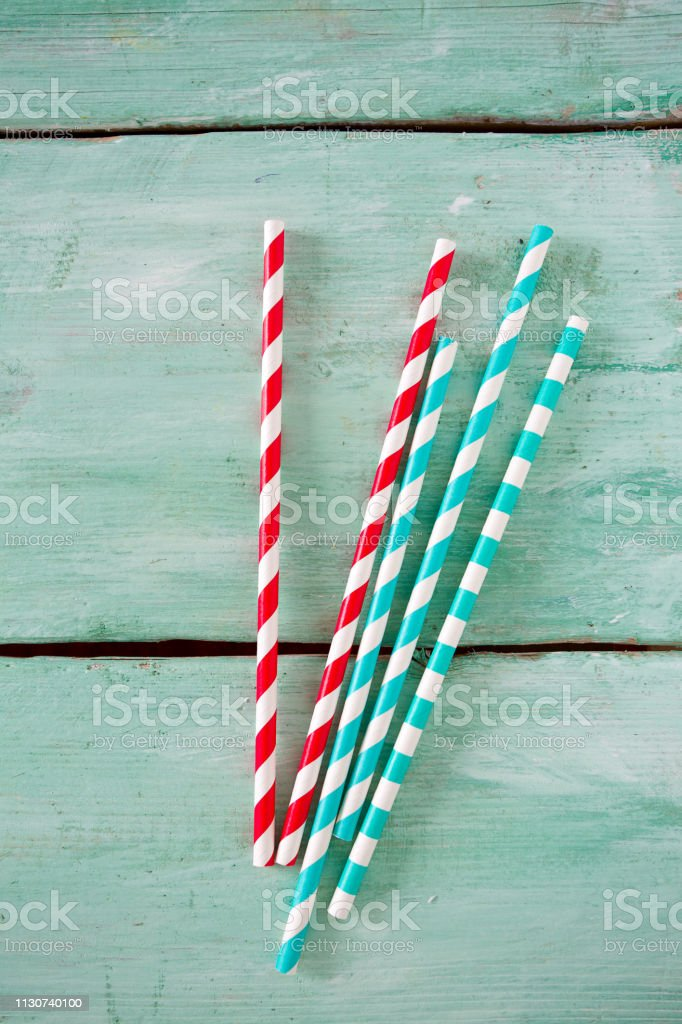 multicolored paper straws on turquoise wooden background