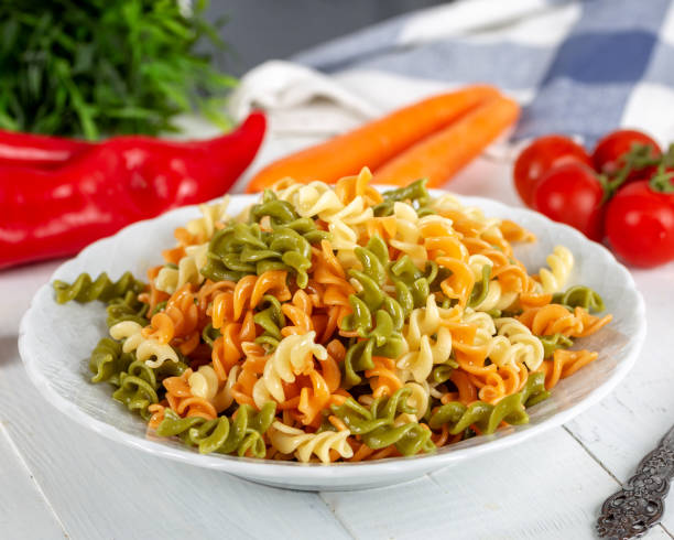 Multicolored pasta with vegetable on wooden background ve vegetables Multicolored pasta with vegetable on wooden background ve vegetables fusilli stock pictures, royalty-free photos & images