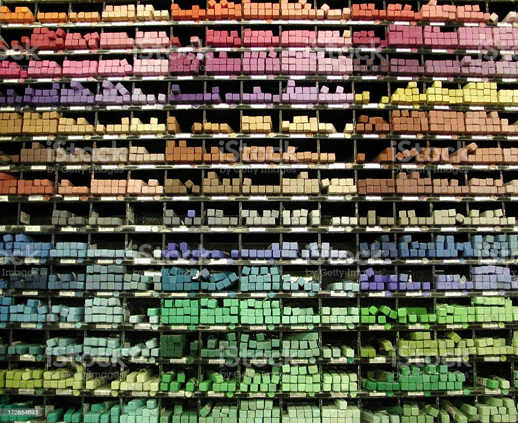 A multicolored shelf of pastels in an art store.
