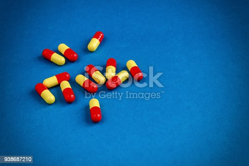 istock Multicolored pills are yellow-red lying on a blue surface. 938687210
