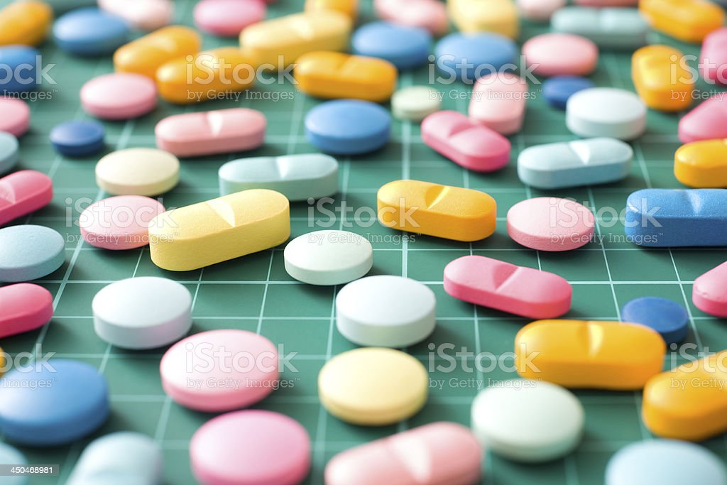 Multicolored pills over measurement grid royalty-free stock photo