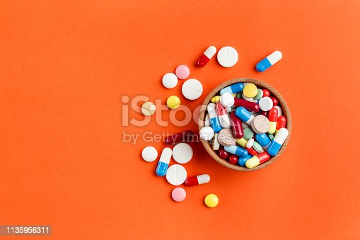istock Multi-colored pills scattered on a bright background, a place for text. 1135956311