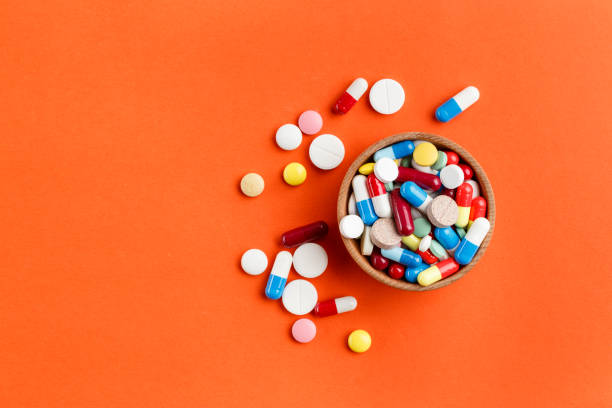 Multi-colored pills scattered on a bright background, a place for text. stock photo