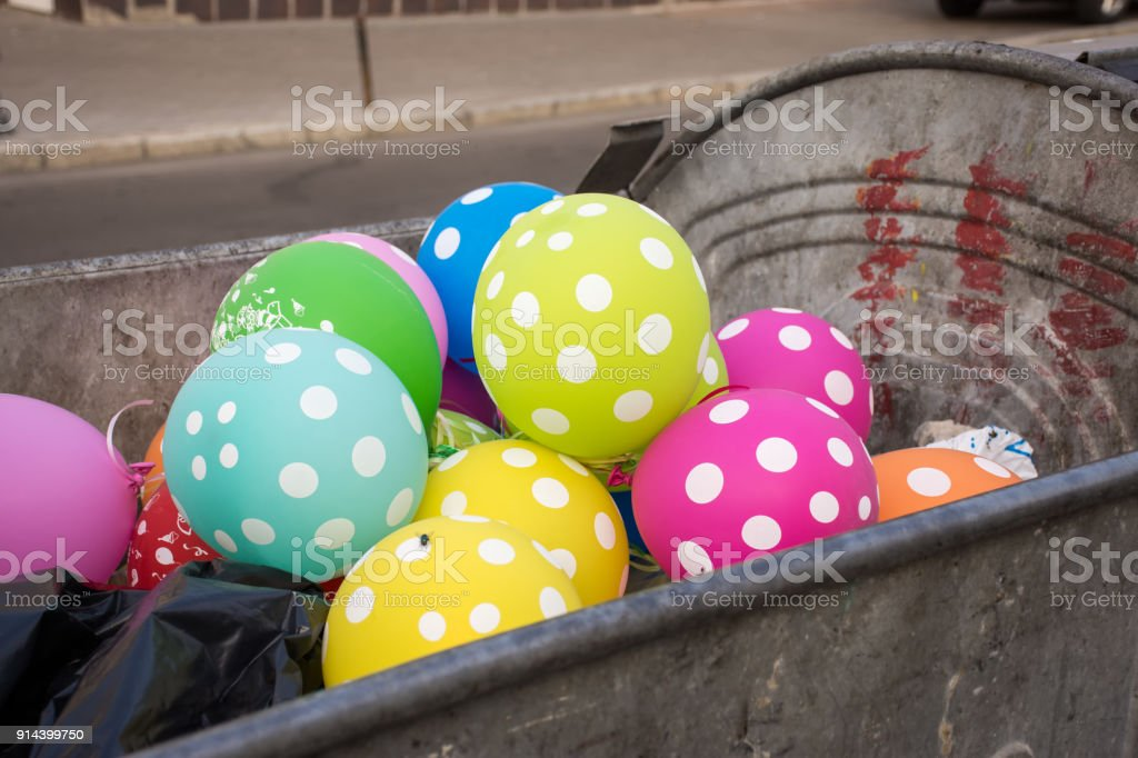 Multi-colored polka dot balloons are in the dumpster or garbage container and on one one sits fly. Party, celebration, fun, holiday, birthday for adult or children is over or ended concept stock photo stock photo