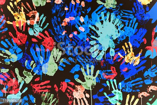 texture of multi-colored prints of hands smeared with paint on a black wall