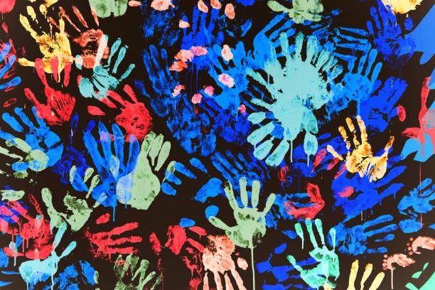 impresiones multicolores de las manos manchadas con pintura en una pared negra - foto de stock