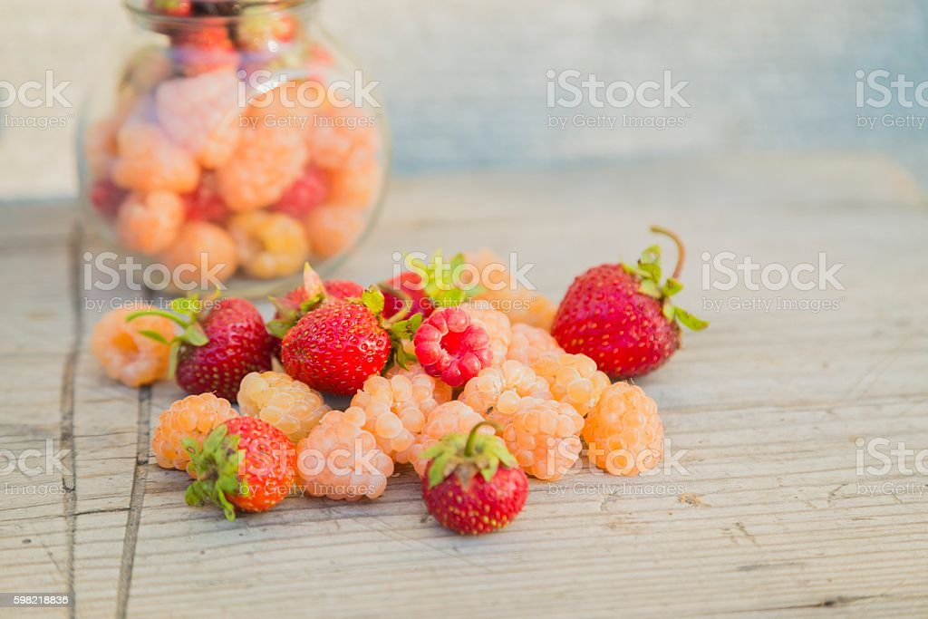 Multicolored raspberries in a glass jar with strawberries on background foto royalty-free