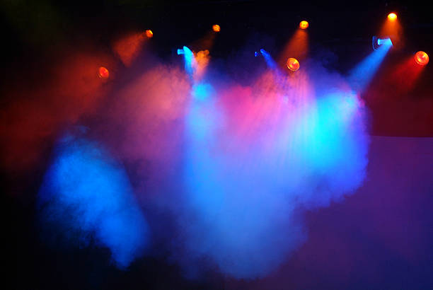 Multicolored Red, Blue and Pink Stage Lights with Fog Horizontal image of dramatic stage lights with fog creating clouds of blue and red. Approximately ten red and blue stage spot lights are shinning from above the stage. The support framework of the lights is not visible. They are shinning onto an empty stage. stage light stock pictures, royalty-free photos & images