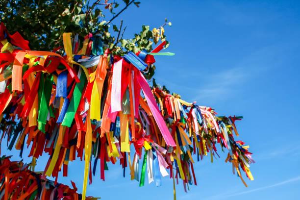 Rubans multicolores sur les branches d'un arbre contre le ciel - Photo