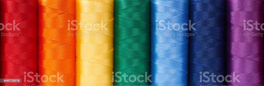 Multicolored sewing threads arrange like rainbow, background - foto de acervo