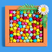 Multicolored small origami stars in box decorated with paper chamomile. Paper art and craft. Trendy hobby. Minimal decorative concept