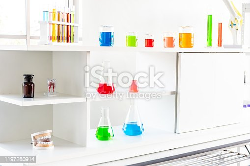 894029864istockphoto Multicolored solutions in experimental glassware on a shelf with a white background in a dental science laboratory. 1197280914