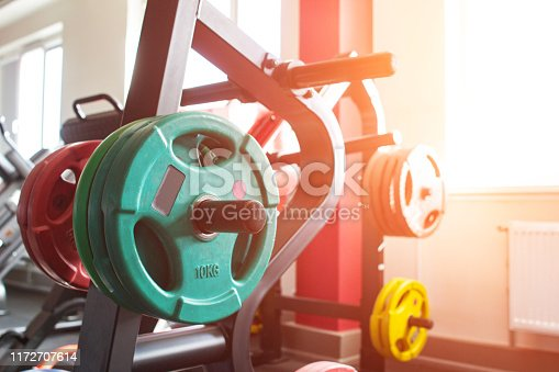 Multicolored stylish metal discs for a barbell in the gym, sunlight, copy space, weightlifting