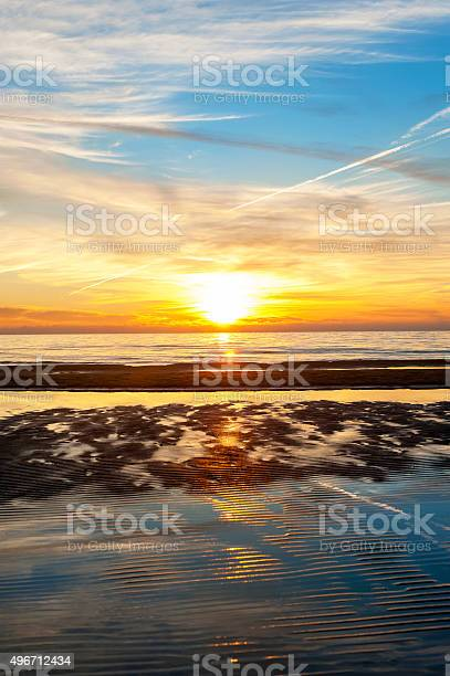 Photo of Multicolored summertime sunset on Baltic sea beach. Vertical outdoors image
