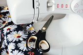 Multicolored textile and tailor scissors lay on sewing machine panel