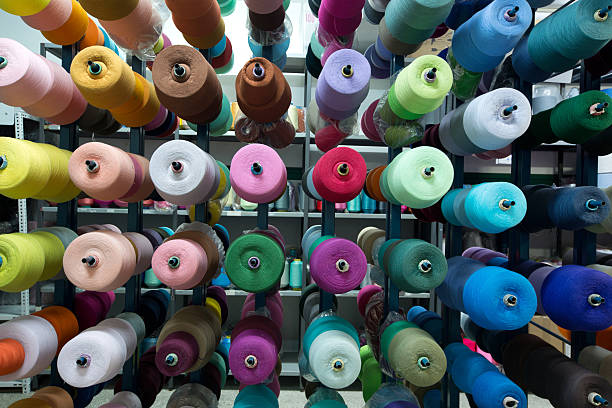 multicolored thread spool in storehouse shelf - garment stock photos and pictures