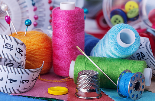 Multi-colored threads on bobbins, needles and pins, sewing kit.