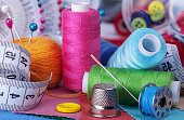 istock Multi-colored threads on bobbins, needles and pins, sewing kit. 1243700399