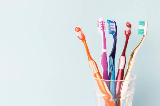 multi-gekleurde tandenborstels in een glazen beker, blauwe achtergrond - streptococcus mutans stockfoto's en -beelden