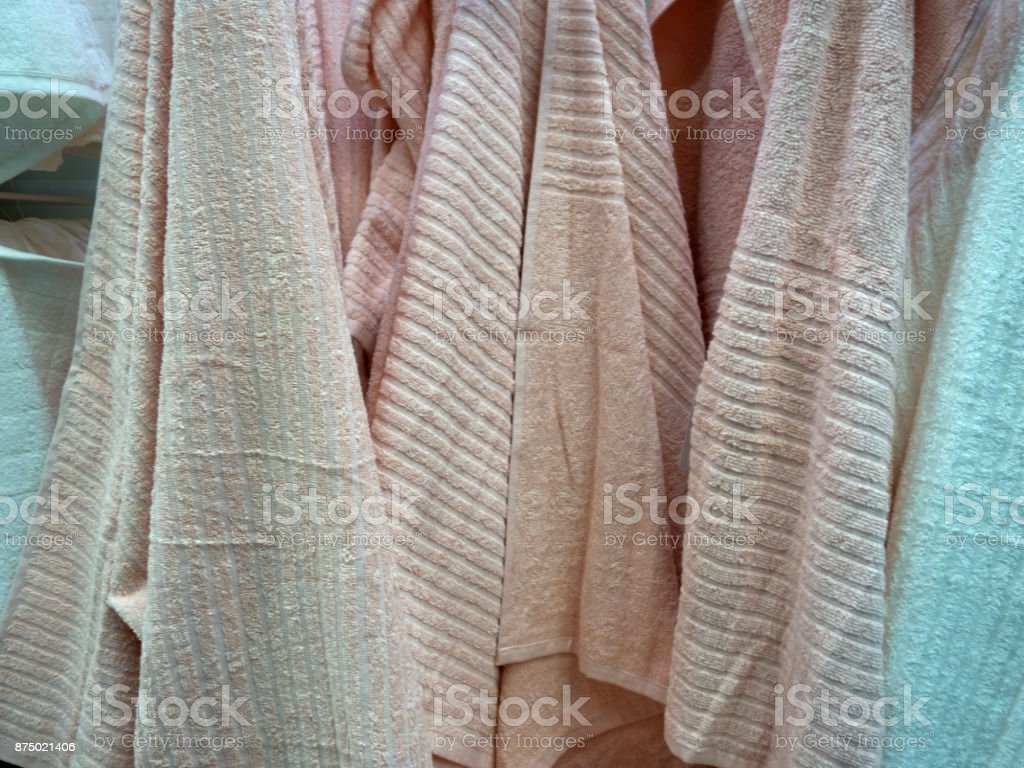 Multicolored towels hang on the hook in the bathroom stock photo