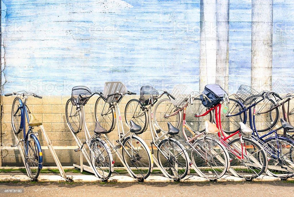 Multicolored vintage bicycles in metal rack in Tokyo city stock photo