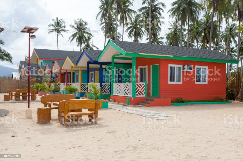 Multi-colored wooden houses on the beach with palms and white sand. Oriental architecture holiday house with large windows and air conditioning. stock photo