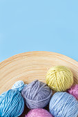 Funny multicolored woolen balls in wooden bowl on blue background. Top view. Close up. Knitting as hobby. Copy space. Vertical format.