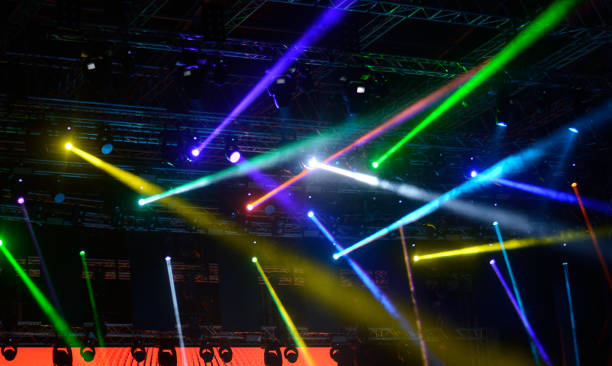 multicolored yellow, blue, green, pink stage lights and video beam - disco lights stock photos and pictures