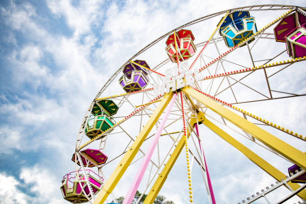 multicolour ferris wheel on blue sky background - carnival stock photos and pictures