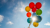 Low angle view of bunch of multicoloured balloons with flares against blue sky.